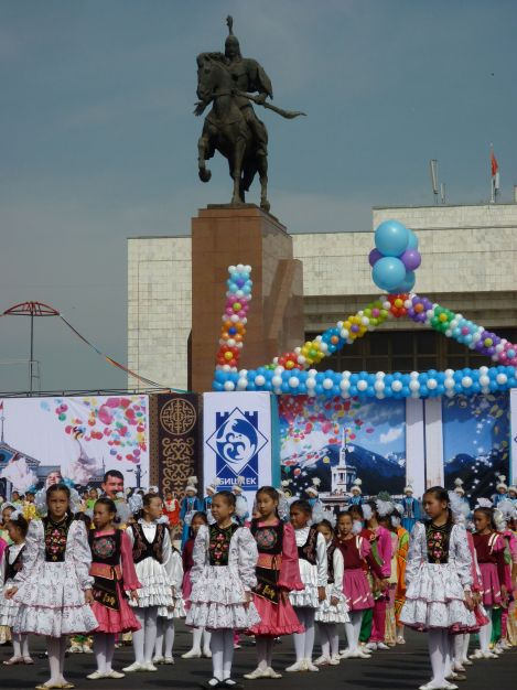 Bishkek's 134th birthday celebration, with a statue of the national hero Manas looming over the dancers.