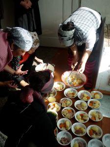 Women preparing goat and potato soup.
