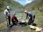 Women boil goat meet in the Kyrgyz mountains. In the background a Russian samovar, a special type of multi-serving tea kettle, has boiled.